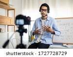 Small photo of Asian school male teacher working from home teaching online math subject to student studying from home. Man using camera to record his live in internet. Remote education class during covid19 pandemic.