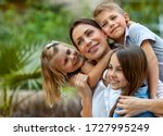 Small photo of Portrait of a nice young mother with pleasure spending time with her three precious kids in the spring park, everyone hugging their lovely mom, having fun together, happy big family enjoying life