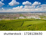 Aerial photo of the city of Leeds viewed from the village of Middleton and Middleton Park on a sunny day with white clouds in the sky.