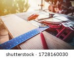 A wooden table full of woodworking tools. Red pencil, meter, angle and miter saw. Craft work theme. - stock photo