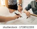 Small photo of Architects engineer discussing at the table with blueprint - Clo