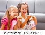 two little girls eating huge...