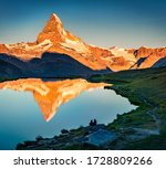 Tourists admiring nice view of Stellisee lake. Splendid evening scene of Matterhorn (Monte Cervino, Mont Cervin) in Swiss Alps, Switzerland, Europe. Beauty of nature concept background. - stock photo