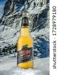 Small photo of MOSCOW, RUSSIA - MAY 07, 2020: Cooled bottle of Miller Genuine Draft Beer with snow on the background of beautiful mountains. Miller beer is a product of the Miller Brewing Company owned by SABMiller.