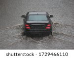 One black car is driving through a big puddle with wave on road during heavy rain, local inundation, rear view