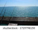Fishing Poles Against A Railin...