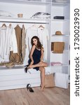 Small photo of Beautiful young woman near rack with hangers.Cheerful young woman sitting near hanger with clothes.walk in closet.Beautiful girl chooses clothes in walk-in closet.
