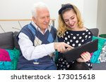Grandfather and granddaughter with tablet - stock photo
