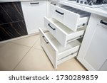 Small photo of Solution for placing kitchen utensils in modern kitchen - horizontal sliding pullout drawer shelves storage in cupboard for kitchenware cookware under oak countertop gas hob with copyspace.