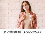 Small photo of Happy hipster girl in stylish medical face mask and jacket drink coffee from paper cup. Beautiful trendy woman in pink protective face mask hold disposable cup of coffee or tea. Quarantine lifestyle