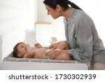 Mother changing baby's diaper on table at home