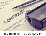 Small photo of Signing a contract under pressure or under duress, business law concept : Pen and a gun or a pistol on a legal contract form, depicting a contract was signed by a coerced or forced person at gunpoint.