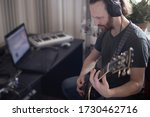 Bearded man musician playing music and composing a song with electric guitar piano and laptop computer while sitting in living room, corona virus quarantine stay home concept - stock photo
