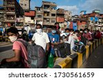 Small photo of MUMBAI/INDIA - MAY 13, 2020: Migrant workers stand in queue at railway terminus for boarding a special train back home during a nationwide lockdown.