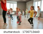 Small photo of Group of little boys and girls dancing while having choreography class in the dance studio. Female dance teacher and children dancing. Contemp dance. Hip hop. Kids and sport. Full length