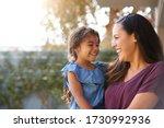 Smiling hispanic mother holding ...