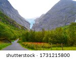 Briksdal or Briksdalsbreen glacier in Olden. Landscape of Norway with huge mountains, forest and road. Foggy and rainy weather. - stock photo