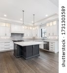 Small photo of CHICAGO, IL, USA - APRIL 23, 2020: A luxurious modern white kitchen with stainless steel Wolf, Subzero, and Whirlpool appliances. A large island sits in the middle with two fancy lights hanging above.
