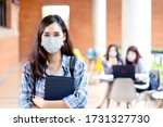 Small photo of Portrait of young asian student wear mask looking at camera holding notebook or tablet in arm in concept come back or return to school, school reopening and unlock after covid or coronavirus outbreak.