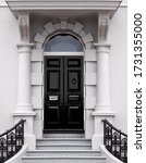 Small photo of London black front entrance door with arch pillars and canopy stone porch