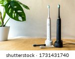 Modern rechargeable sonic or electric toothbrush set with charger in bathroom. Concept of professional oral care and healthy teeth by using ultrasonic smart toothbrush. Minimal design