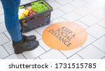 Small photo of store markings on the floor, keep a social distance. a woman stands near a marking on the floor, next to a basket of food and vegetables.