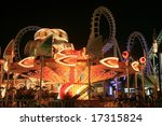 Blurry / long exposure image of a brightly lit amusement park rides - stock photo