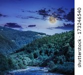 wild river flowing between green mountains in moon light - stock photo