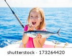 Small photo of Blond kid girl fishing tuna little tunny happy with trolling catch on boat deck