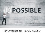 "Small photo of Businessman turning the word ""Impossible"" into ""Possible"""