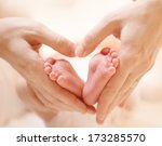 Baby Feet In Mother Hands. Tin...
