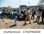 Small photo of MUMBAI/INDIA - MAY 14, 2020: Police personnel weilding lathis disperse a crowd flouting social distance outside railway terminus for boarding a special train back home during a nationwide lockdown.