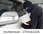 Car theft breaking and entering into  a car using a screwdriver to open front door. - stock photo