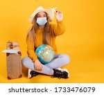 Small photo of A tourist girl with a medical mask, outbreak of coronavirus COVID-19. Concept of canceled trips. A tourist cannot leave due to a pandemic.