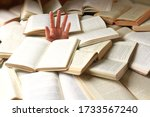 Small photo of A student or reader drowned in a mountain of books. Man's hand sticks out from the rubble of open books. Concept - preparing for exams or excess information. Selective focus.