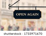 Small photo of Open again sign board against open shop windows background. Restarting business after coronavirus quarantine lockdown. Economy reopening concept