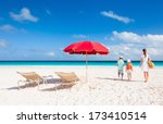 Two chairs under umbrella on a beautiful tropical beach with family walking nearby - stock photo