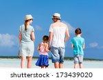 Happy beautiful family walking at beach during summer vacation - stock photo