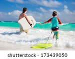 Mother and son running towards ocean with boogie boards - stock photo