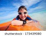 Little boy on vacation having fun swimming on boogie board - stock photo