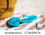 Straw bag, towel and flip flops on a tropical beach - stock photo
