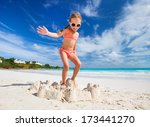 Little girl at tropical beach jumping on a sand castle having fun  - stock photo