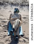 Small photo of Beach life in age of coronaviruses. Man in protective suit, ABC-protective mask (box respirator) is sunbathing on sand. How will life change after Covid-19 - changing social paradigm concept