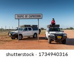 Asian woman traveler posing on camper car at tropic of capricorn sign in Namibia. Road trip travel in Africa concept.
