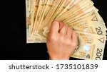 hand with polish zloty isolated on black background, Hand holding polish zloty, Trading Business Theme, two hundred money banknotes - stock photo