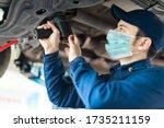 Small photo of Mechanician changing car wheel in auto repair shop wearing a mask, coronavirus concept