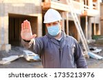 Caucasian foreman wearing mask and hardhat at construction site, building in background. Concept of coronavirus social distance and covid-19. - stock photo