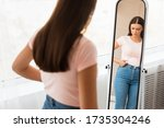 Small photo of Unhappy Woman Gaining Excess Weight Touching Drooping Belly Standing At Mirror At Home. Unsuccessful Diet. Selective Focus