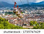 Picturesque aerial view of Grenoble city, Auvergne-Rhone-Alpes region, France. Grenoble-Bastille cable car on the foreground. French Alps on the background
