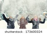 Three teenage girls throwing snow in the air.